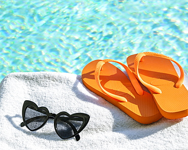Orange flip flops and heart shaped sunglasses on towel at poolside