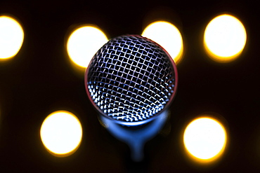 Close-up of microphone with stage lights in background