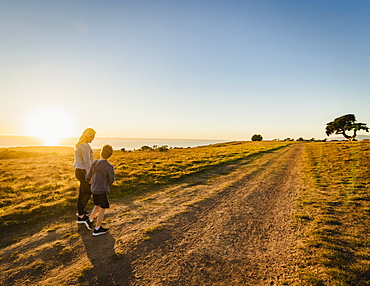 United States, California, Cambria, Rear view of mother and son (10-11) walking in landscape at sunset