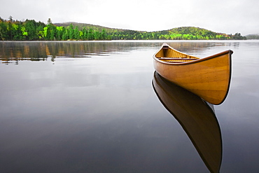 United States, New York, Saranac Lake, Wooden canoe floating on calm Upper Saranac Lake