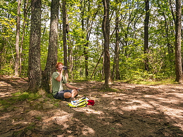 United States, Virginia, Hiker drinking in forest