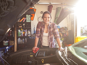 Woman fixing car in garage