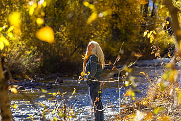 United States, Idaho, Sun Valley, Senior woman standing in sunlight by river in autumn