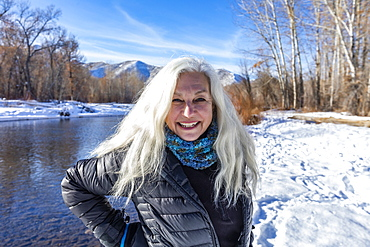 United States, Idaho, Bellevue, Outdoor portrait of smiling senior woman with long white hair in winter landscape