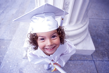 Portrait of girl (4-5) in white graduation cap and gown