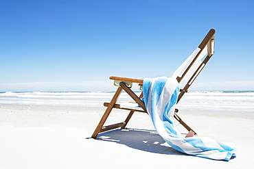 Empty beach chair with striped towel on beach