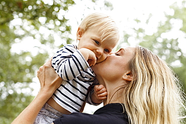 Mother kissing baby girl on cheek, outdoors