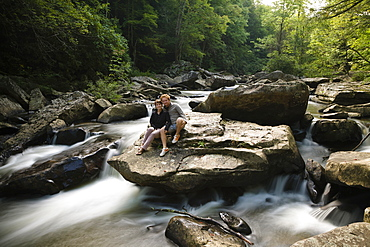 Portrait of mid adult couple, sitting together on rock in waterfall, New River Gorge National River, Fayetteville, West Virginia, USA