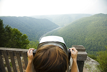Mid adult woman looking through coin operated binoculars, rear view, New River Gorge National River, Fayetteville, West Virginia, USA