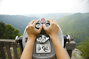 Mid adult woman holding coin operated binoculars, focus on hands, New River Gorge National River, Fayetteville, West Virginia, USA