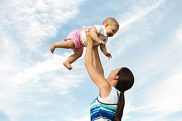 Mid adult woman holding up baby daughter against blue sky