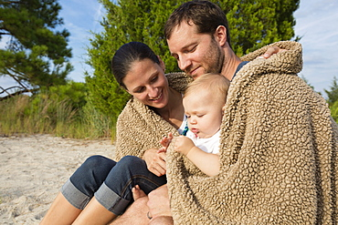 Mid adult parents and baby daughter sitting on sand wrapped in blanket