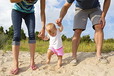 Mid adult parents holding baby daughters hands while toddling in sand