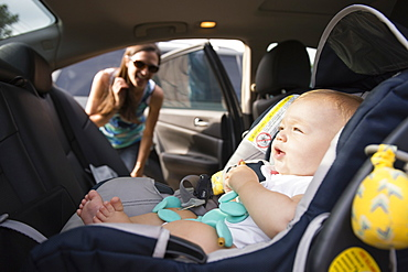 Mid adult woman checking safety belt on baby daughters car seat