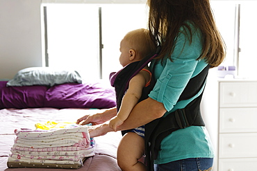 Mid adult woman doing chores with baby daughter in baby sling