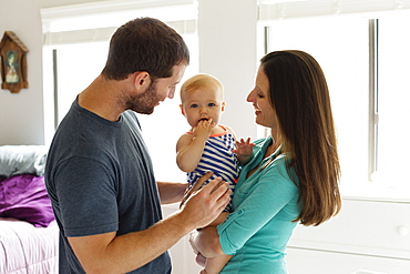 Portrait of mid adult couple with baby daughter in bedroom