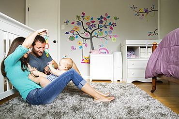 Mid adult couple playing with baby toy and baby daughter on lap