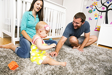 Mid adult couple playing with baby daughter on nursery rug