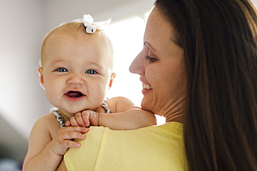 Over the shoulder portrait view of happy baby girl and mid adult mother