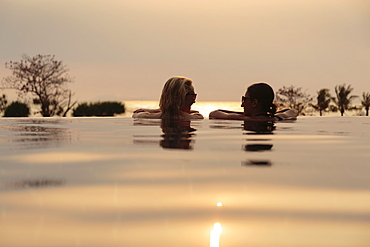 Rear head and shoulder view of two women chatting in rural infinity pool at sunset, Kep, Cambodia