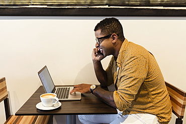 Young man in coffee shop, using laptop and smartphone