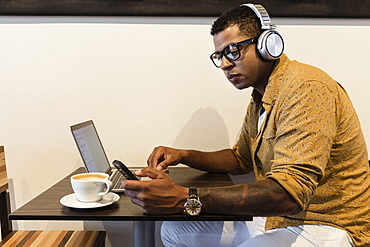 Young man in coffee shop, wearing headphones, using laptop and smartphone
