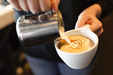 Coffee shop barista pouring milk into coffee, mid section, close-up