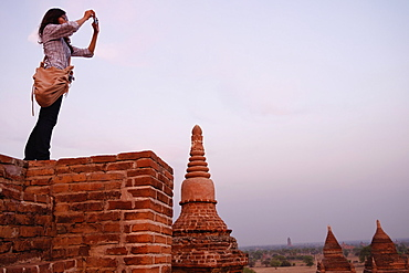 Woman taking photograph of view, Bagan Archaeological Zone, Buddhist temples, Mandalay, Myanmar