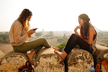 Women relaxing on stone wall, Bagan Archaeological Zone, Buddhist temples, Mandalay, Myanmar