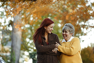 Senior woman and adult daughter strolling in suburban park