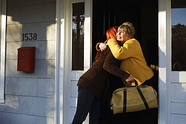 Senior woman and adult daughter hugging at front door
