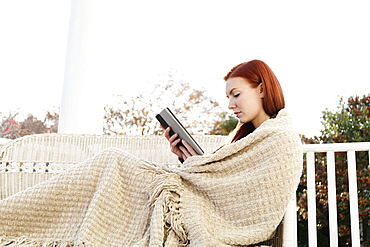 Young woman wrapped in blanket reading digital tablet on porch