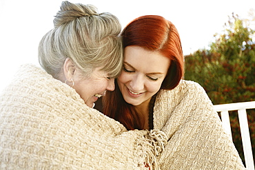 Senior woman and adult daughter face to face wrapped in a blanket on porch