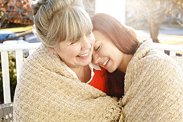 Senior woman and adult daughter wrapped in a blanket on porch