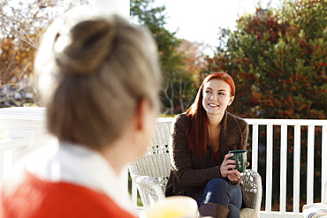 Senior woman and adult daughter chatting and drinking coffee on porch