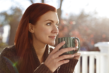 Young woman drinking coffee and gazing out from porch