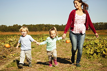 Mother with two children running in pumpkin field