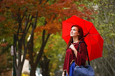 Young woman with red hair, holding red umbrella