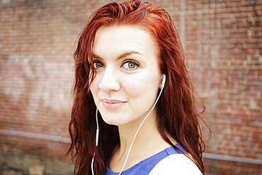 Portrait of young woman with long red hair, wearing earphones, close-up