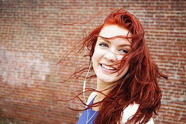 Young woman with long red hair, wearing earphones, close-up
