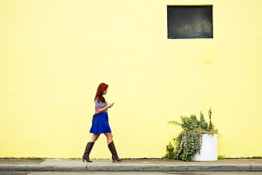 Young woman with red hair, walking along street