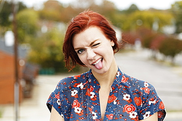 Young woman with red hair, sticking her tongue out