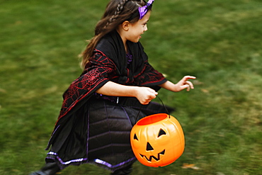 Girl in fancy dress costume with trick or treat bucket