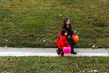 Two girls in fancy dress costumes walking down path