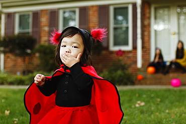 Girl dressed as ladybird with hand on mouth