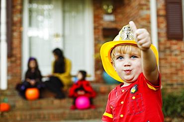 Boy wearing fireman's helmet