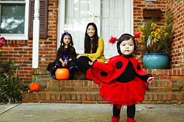 Girl dressed as ladybird outside house