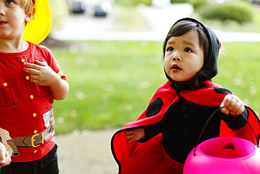 Girl and boy wearing fancy dress costumes with trick or treat bucket