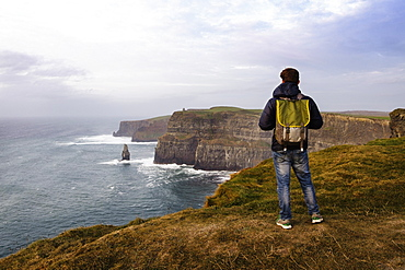 Mid adult man standing on The Cliffs of Moher, The Burren, County Clare, Ireland