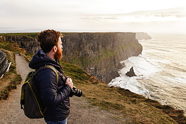 Mid adult man on The Cliffs of Moher with camera, The Burren, County Clare, Ireland
